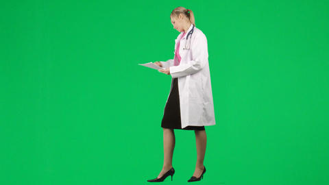 Female doctor writing notes against green screen Footage