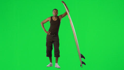 Ethnic boy with a surfboard against green screen Stock Video Footage