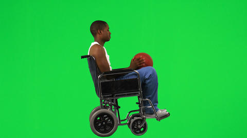 Ethnic boy on a wheelchair playing with a basket b Footage