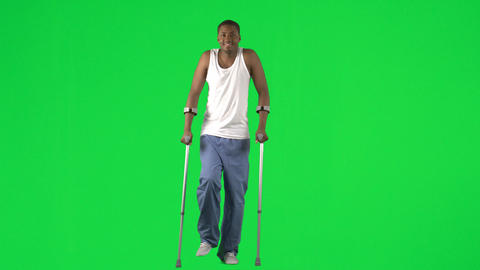 Ethnic young man walking with crutches footage Footage
