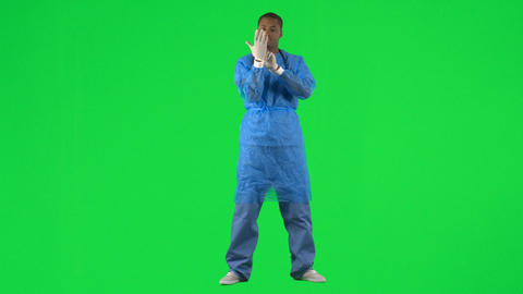Ethnic surgeon putting on gloves against green scr Stock Video Footage