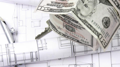 Close up of plans, dollar house and keys turning Footage