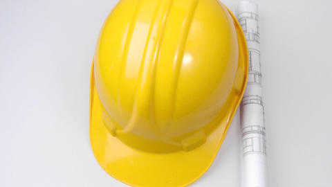 High view of a yellow hard hat and a plan turning Footage