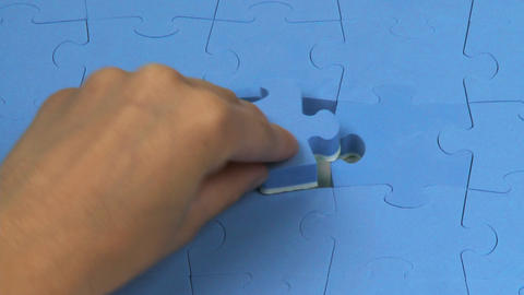 Hand placing the last piece on a puzzle Footage