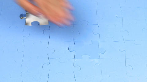 Hand placing the last two pieces on a puzzle Footage