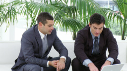 Two businessmen sitting on sofa using a laptop Footage