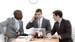 Three businessmen in a meeting using a laptop and Stock Video Footage