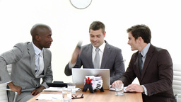 Three businessmen in a meeting using a laptop and talking on phone Footage