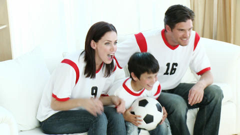 Family in Living Room watching Sport on TV Live Action
