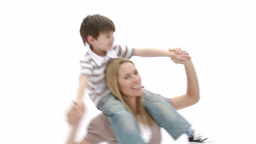 Woman giving little boy piggyback ride Stock Video Footage