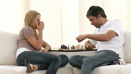 Couple playing chess on sofa in livingroom Footage