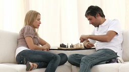 Couple playing chess on sofa in livingroom Stock Video Footage