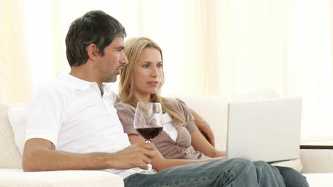Couple using a laptop and drinking wine Footage