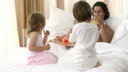 Happy family having breakfast in bed Footage