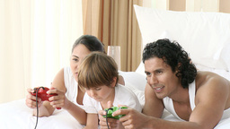 Family playing video games in bed Stock Video Footage
