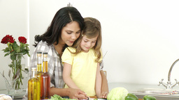 Mother and little girl cutting vegetables Footage
