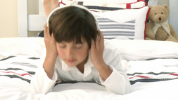 Boy relaxing on bed listening to the music Footage