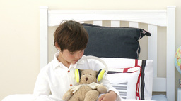 Boy playing with a teddy bear and headphones in bed Stock Video Footage