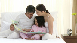 Parents reading a book on bed with their daughter Stock Video Footage
