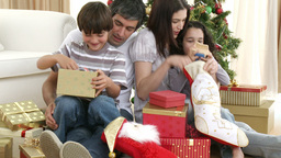Parents and children opening Christmas presents Stock Video Footage