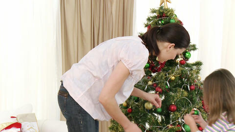Mother and little girl decorating Christmas tree Stock Video Footage