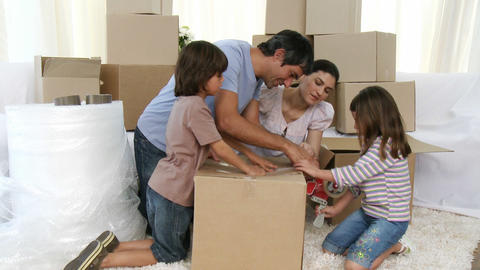 Parents and children moving house packing boxes Footage