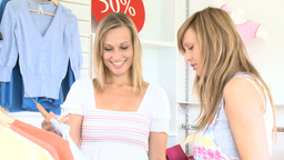 Two bright women choosing clothes together Stock Video Footage