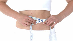 Young beautiful woman measuring her waist with a t Footage