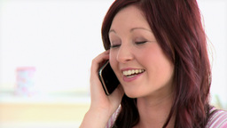 Joyful young woman sitting on sofa and phoning Footage