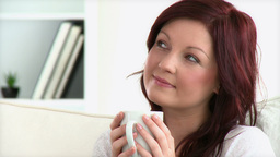 Relaxed woman enjoy her coffee sitting on a sofa Footage