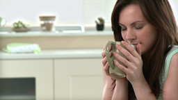 Relaxed woman drinking coffee in the kitchen Footage