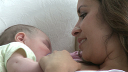 Smiling young mother lying on a sofa with her baby Footage
