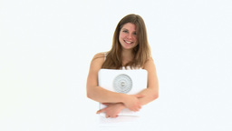 Happy young woman holding a scale Footage