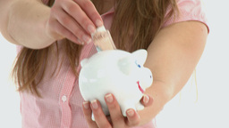 Close up of woman putting money in a piggybank Footage