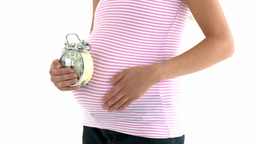 Close up of a pregnant woman holding an alarm cloc Footage