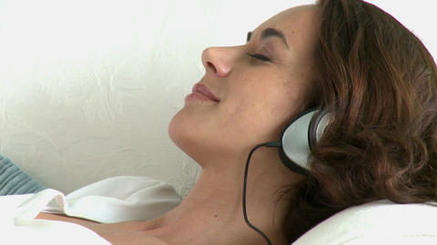 Relaxing hispanic woman lying on the sofa and listening to music with headphones Footage