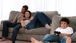 Family on the sofa watching his son playing video  Footage