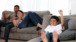 Family on the sofa watching his son playing video Stock Video Footage