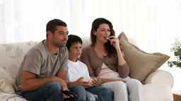 Loving family watching television sitting on sofa Footage