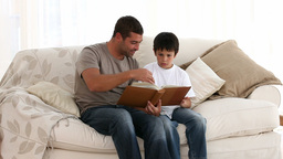 Father and son with a book in the sofa Footage