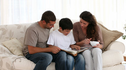 Family reading on sofa Stock Video Footage