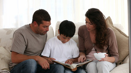 Family reading on the sofa Stock Video Footage