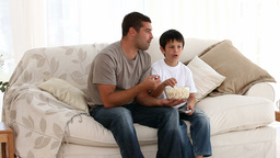 Father eating popcorn with his son Stock Video Footage