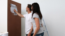 Couple painting wall in white Stock Video Footage