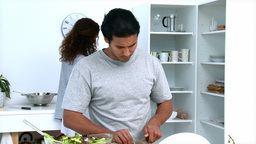 Concentrated man cutting vegetables with his girlf Stock Video Footage