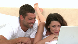 Happy couple using laptop lying on the bed Footage