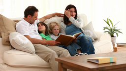 Cute family looking at an album Stock Video Footage