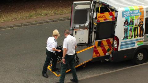 Female paramedic pushing a wheelchair into ambulan Footage