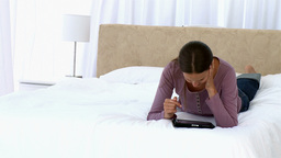 Girl using a tablet lying on the bed Stock Video Footage