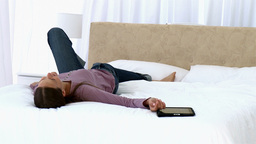 Girl using a tablet lying on the bed Footage